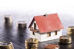 Haus und Stapel mit Münzen